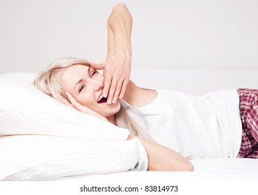 beautiful young blond woman waking up, yawning and stretching on the bed at home