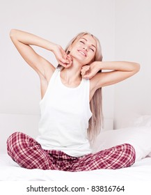 beautiful young blond woman waking up and stretching on the bed at home