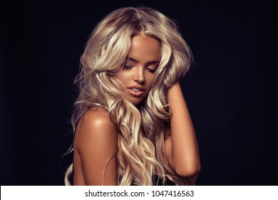 Beautiful young blond woman with wavy long hair posing in the studio on the black background