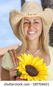 A beautiful young blond woman wearing a straw cowboy hat and smiling while carrying a shopping bag of sunflowers