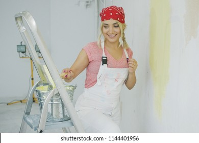 Beautiful young blond woman in white overalls and red bandana dipping brush into metal bucket with pastel yellow wall paint placed on top of stepladder