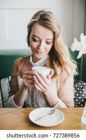 Beautiful young blond woman in a white dress enjoying coffee cappuccino with foam near window in a cafe