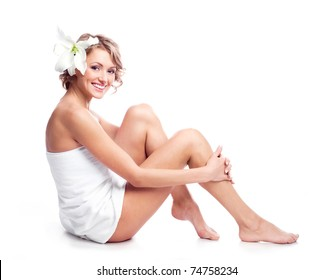 beautiful young blond woman wrapped into the towel  with a lily in her hair