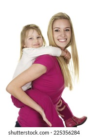 Beautiful Young Blonde Babysitter giving a cute little girl  a piggy back ride on a white background