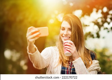 Beautiful young blonde Caucasian woman with takeaway coffee taking a selfie with smartphone outdoors in park in autumn.