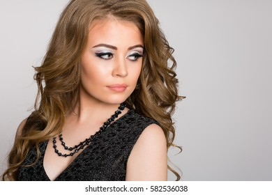 Beautiful young blonde with curly hair on a gray background