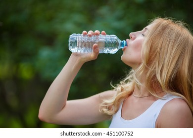 Beautiful young blonde drinks water in park