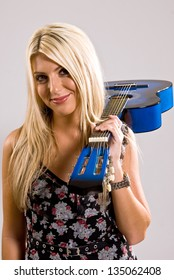 A beautiful young, blonde, female holding a blue guitar over her shoulder in a floral print dress with a smile on her face.