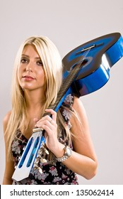 A beautiful young, blonde, female holding a blue guitar over her shoulder in a floral print dress and a look of attitude on her face.