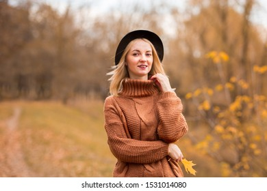 beautiful young blonde girl in a brown warm sweater, black felt hat smiling. In the background are yellow autumn trees. horizontal photo in the park