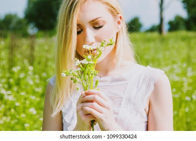 Beautiful young blonde girl in field enjoying the sun and smelling the flowers in hand, white, transparent dress