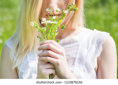 Beautiful young blonde girl in field smelling flowers in hand, white, transparent dress, blurred background