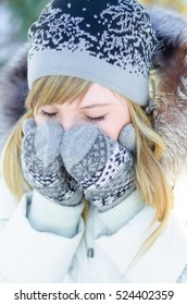 Beautiful young blonde girl in hat and mittens covering her face and eyes on the street in the cold