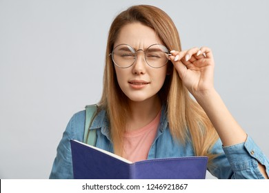 Beautiful young blonde girl holding glasses and squinting trying to read the inscription in front of her. Girl student with poor eyesight have difficulty reading small text.