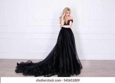 Beautiful young blonde girl in a long black dress