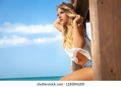 Beautiful young blonde girl looking out over the sea. Long blond hair and relaxing time on vacation. Sitting in a wooden building.