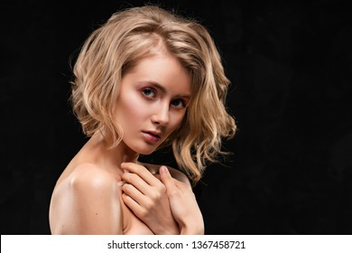 Beautiful young blonde girl with naked shoulders and curly hair, posing, with her hands sensually pressed to her breast, on a black background. Clean, healthy skin. Close-up. Copy space.