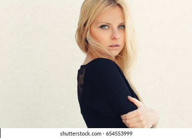 Beautiful young blonde girl on white background close-up portrait.