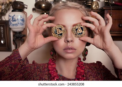 beautiful young blonde girl in retro interior in motley Turkish dress, brooches, earrings and a large red the necklace