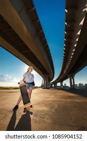 Beautiful young blonde girl riding longboard in sunny weather
