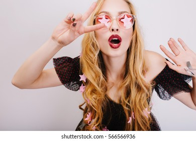 Beautiful young blonde girl showing peace with opened mouth, having fun, posing to camera, celebrating event. Wearing pink cool glasses, black dress, has nice long curly hair. Isolated background.