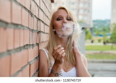 Beautiful young blonde girl smokes a white cigarette on a brick wall background on a street in the city