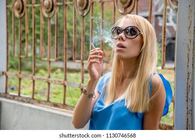 Beautiful young blonde girl smokes a white cigarette outdoors in a city in summer