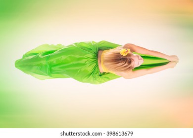Beautiful young blonde girl in a yellow top, a long green skirt and a hairpin with a flower on her head dancing view from above. Toned