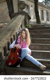 Beautiful Young Blonde Hair Model with Guitar Sitting on the Staircase in the Park on Sunny Spring Day