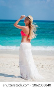 Beautiful young blonde hair woman with sun hat in bikini swimwear and long white skirt. Summer vacation  happy beach scene