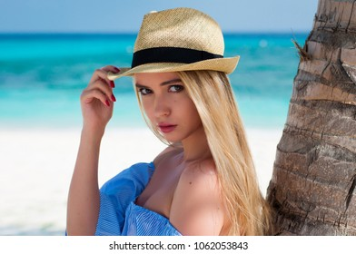 Beautiful young blonde hair woman with sun hat and bare shoulders near palm tree. Summer vacation  happy beach scene
