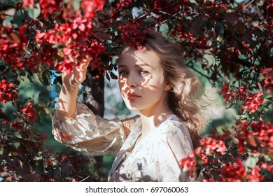 Beautiful young blonde hair woman with shadows on her face with blossom apple trees in spring garden