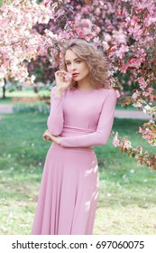 Beautiful young blonde hair woman in long pink dress with blossom cherry trees in spring garden
