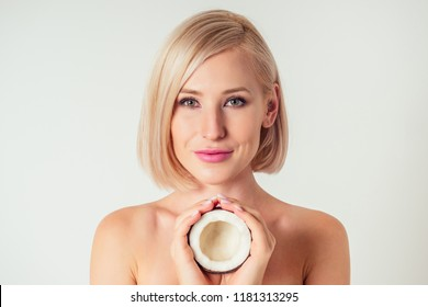 Beautiful young blonde hairstyle girl with a long eyelashes make-up and perfect skin with coconut in her hand in the studio on a white background. Beauty face hair care.