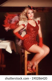 A beautiful young blonde lady is posing in an old pub and restaurant. She is wearing various Broadway performer outfits.