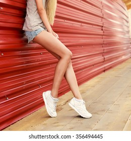 Beautiful young blonde long legs woman posing outdoor in summer sensual fashion hipster sport style on red background in jeans shorts and white sneakers