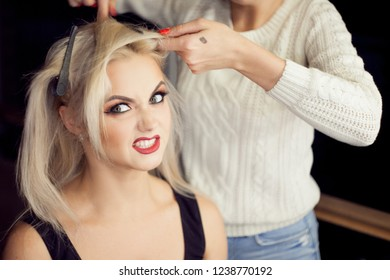 Beautiful young blonde. Makeup artist makes hair. Close-up dark background