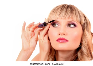 Beautiful young blonde woman applying mascara on her eyelashes