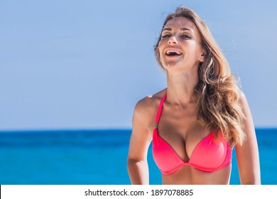 Schöne junge Blonde in Bikini lacht am Strand
