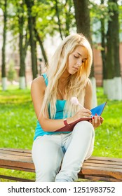 Beautiful young blonde woman in blue t-shirt sits on bench and writes in notebook against background of green summer city park.