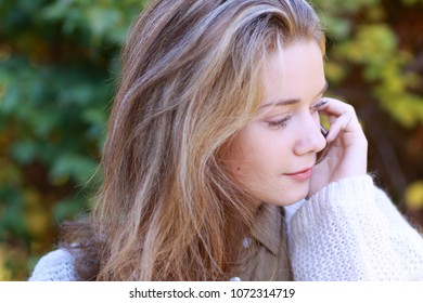 Beautiful young blonde woman calling by phone in autumn park