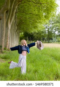 Beautiful young blonde woman dancing in the countryside in summertime