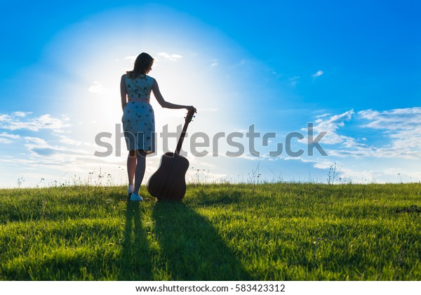 beautiful young blonde woman in dress holding the guitar on sunset or sunrise sky and green field background Copy Space for inscription