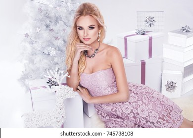 Beautiful young blonde woman in elegant pink dress sitting next to white christmas tree and presents. Christmas glamour photo
