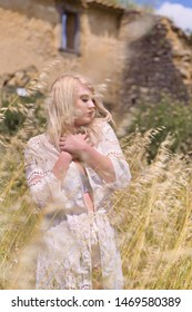 Beautiful young blonde woman enjoying nature in a field with high grasses