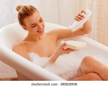 Beautiful young blonde woman enjoying pleasant bath with foam, putting shower gel on a wisp of bast and smiling