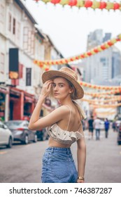A beautiful young blonde woman exploring pretty part of Chinatown in Singapore. Hot weather in the colorful small urban downtown. She wears casual combination of clothes with a nice hat.