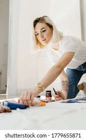Beautiful young blonde woman getting ready to paint at home. Choosing instrument to paint. many painting oil colors and paint brushes on the floor.