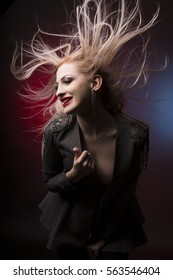 Beautiful young blonde woman with hair in motion at studio