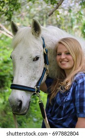 A beautiful young blonde woman and her white steed